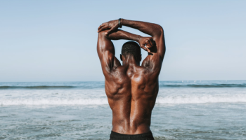 Man Stretching his arms, facing the ocean. Resource: Pexels