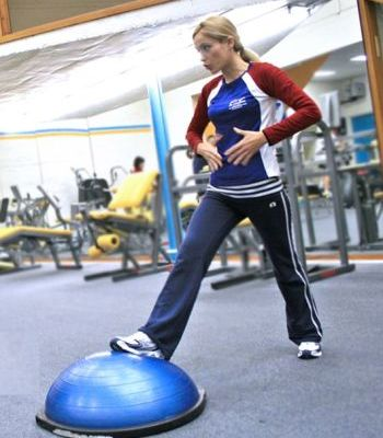 Woman at the Gym Instructing on Bosu Ball Use